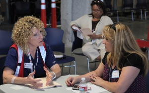 """Health Services Volunteer Susan Hawkins speaks with a """"passenger"""" in the family reunification center."""