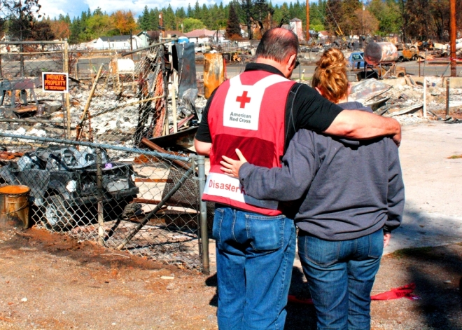 Red Cross volunteer Andy Grossman talks with Weed resident Karly Gregory at the site where her home once stood.