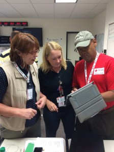 Volunteers Sharon Andrews, Debbie Gentry-Rao, and Gregory Small discuss needs at the fire sites.