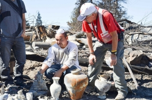 Volunteer Paul Keeton helps members of the Lee family as they go through the remains of their home in Weed.