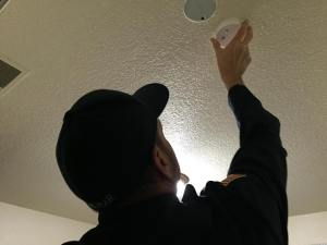 Turlock Firefighter, Scott Wejmar, installs a smoke detector during the November canvass event.