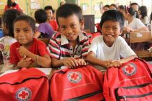 "September 3, 2015. Tolosa, Leyte, Philippines Children from Tanghas Elementary School show off their new Red Cross backpacks. The students continue to enjoy their school, repaired with funds from the American Red Cross in 2014 in partnership with the Spanish Red Cross. Children received backpacks full of supplies to start the school year. The Red Cross installed hand water pumps, constructed six new latrines, and repaired classrooms that were badly damaged by Typhoon Haiyan. Even though it was ravaged by high winds and fallen coconut trees, about 20 families used the school as a shelter in the aftermath of the typhoon. One hundred and thirty-two students, from kindergarten to sixth grade, attend Tanghas Elementary School. The school's five teachers all survived the storm and returned to teach this year. All the surrounding schools are full, so if this one wasn't able to reopen, they'd have nowhere else to get their education. The Red Cross trains local people on carpentry, plumping, electrical and construction skills and then pays them to repair schools like Tanghas Elementary. ""Without the Red Cross repairing the school, I don't know what would happen to our children,"" said school official, Noresita A. Go. This project is in collaboration with the Spanish Red Cross. Photo by Niki Clark/American Red Cross"