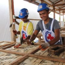 September 1, 2015. Dulag, Leyte, Philippines Reynan Cayubit, 29, and Francisco Latoja, 27, work as carpenters at a Red Cross workshop that build houses for Typhoon Haiyan survivors. Both of their houses were destroyed by the typhoon and they have both since rebuilt them using the money they earn at the workshop. Francisco is now paying for his wife to go to school to become a teacher with the money he earns. In an effort to put people back to work after the storm, the American Red Cross trains local carpenters and pays them to construct the houses from start to finish. This project is in collaboration with the German Red Cross. Photo by Philippines Red Cross/ Thyjiacinth Ylla Mavourneen Dyde Ocampo 2015