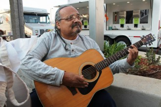 Joe Avila sitting with his guitar outside of a Red Cross shelter.